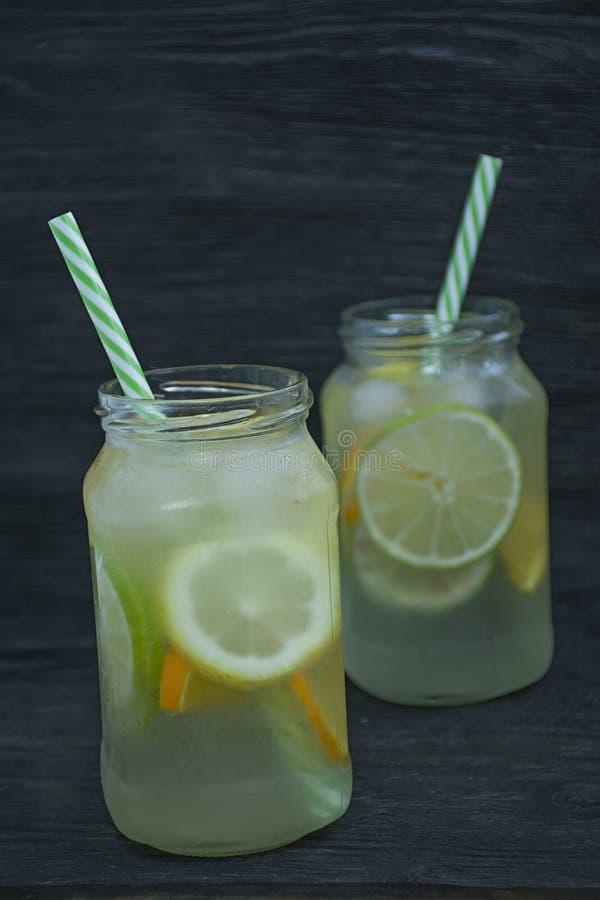 Auffrischungssommergetränk von den Zitrusfrüchten Getränk vom Kalk, Zitrone, Orange Dunkler h?lzerner Hintergrund stockfoto