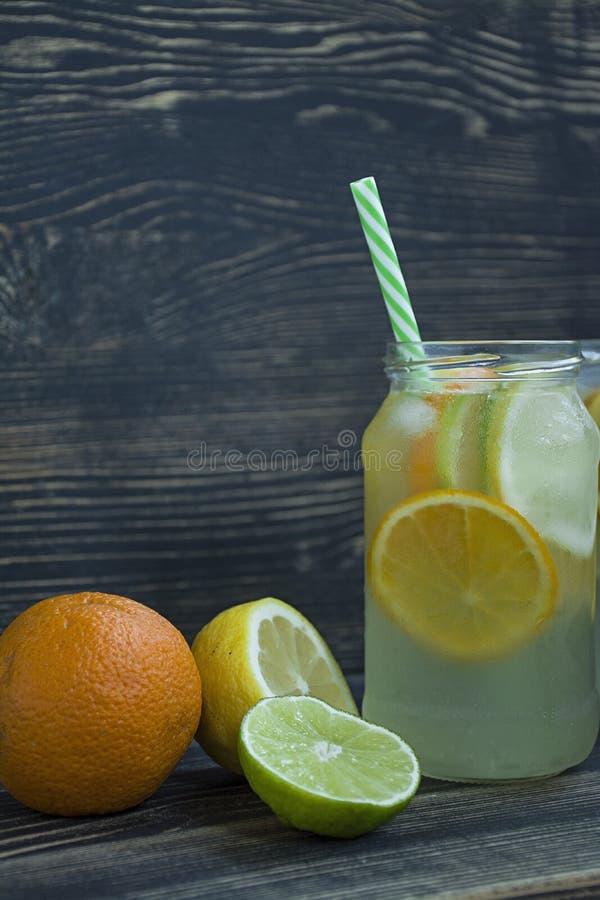 Auffrischungssommergetränk von den Zitrusfrüchten Getränk vom Kalk, Zitrone, Orange Dunkler h?lzerner Hintergrund Raum f?r Text stockfotografie