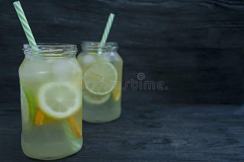 Auffrischungssommergetränk von den Zitrusfrüchten Getränk vom Kalk, Zitrone, Orange Dunkler h?lzerner Hintergrund Raum f?r Text lizenzfreie stockfotografie