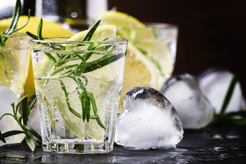 Auffrischungszitrone trinken mit Rosmarin, Eis und Stärkungsmittel, schwarzer Stein stockbild
