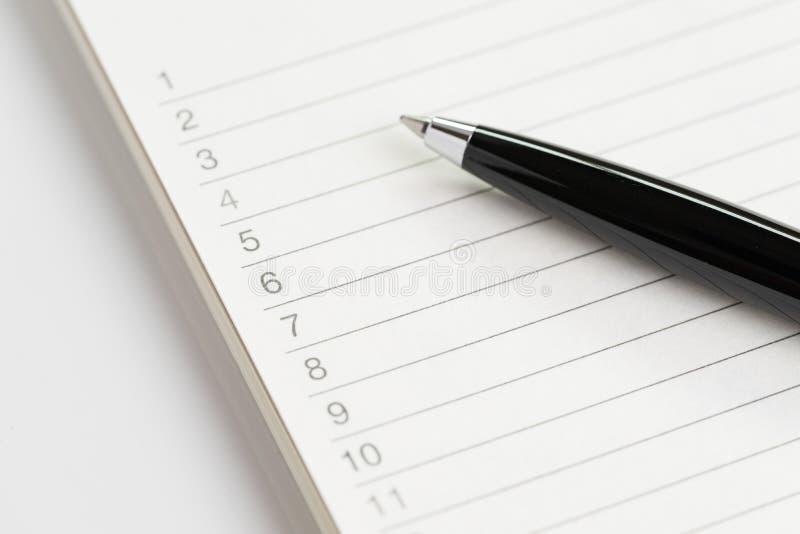 Aufgabenlisten- oder Einkaufswunschlistekonzept, durch oben geschlossen vom schwarzen PET lizenzfreies stockfoto
