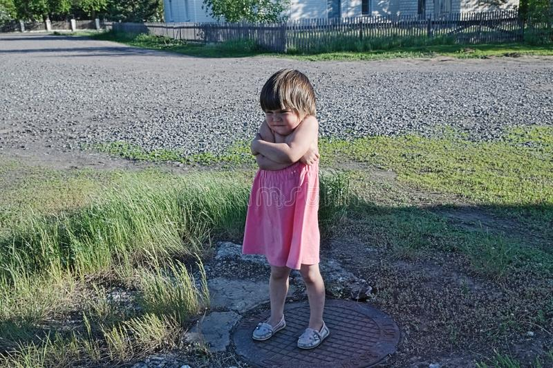 Aufgebrachtes Kind steht und zieht ` t möchten überall gehen verteidigen kleines Mädchen der eigenen Position in den rosa sundres stockfotografie