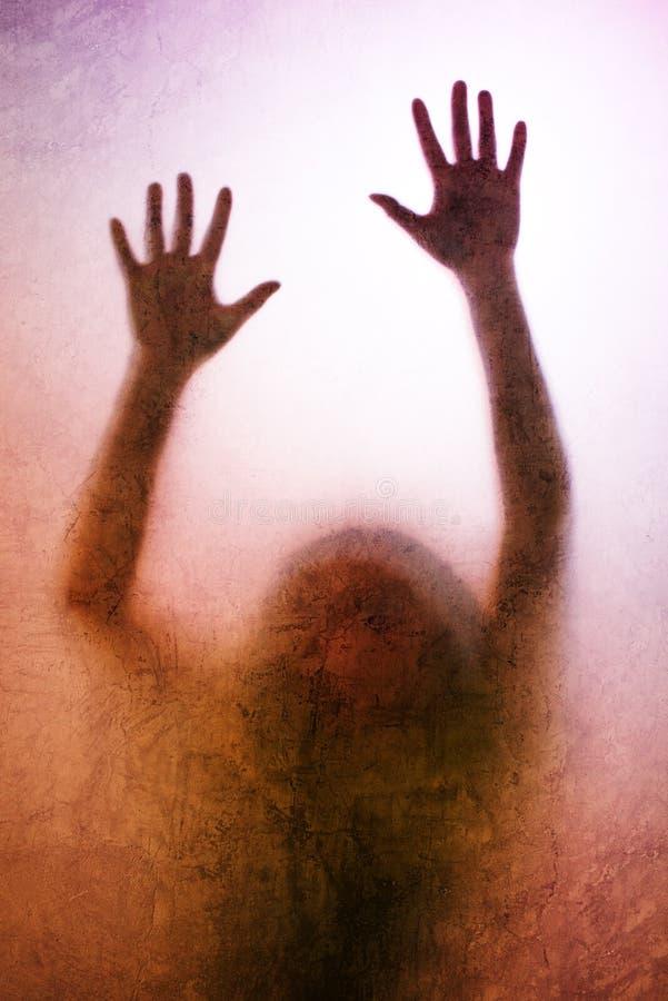 Aufgefangene Frau, hintergrundbeleuchtetes Schattenbild von Händen hinter Mattglas stockbild