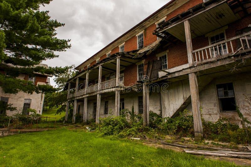Aufgegebene Gebäude u. überwucherte Anlagen - verlassenes Armenhaus lizenzfreie stockfotos