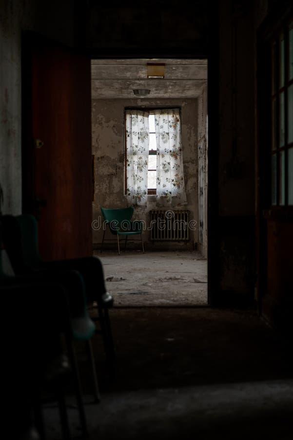 Aufgegebener Raum mit grünem Plastikstuhl, Heizkörper u. Vorhängen - verlassenes Westboro-staatliches Krankenhaus - Massachusetts lizenzfreies stockbild