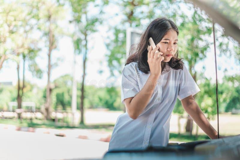 Aufgegliedertes Autokonzept Junge Frau, die sie aufgegliedertes Auto betrachtet stockbilder