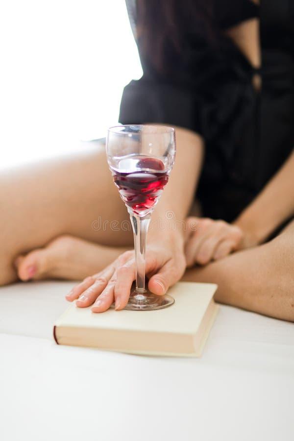 Aufgehaltenes Glas Rotwein auf Weißbuch lizenzfreies stockbild