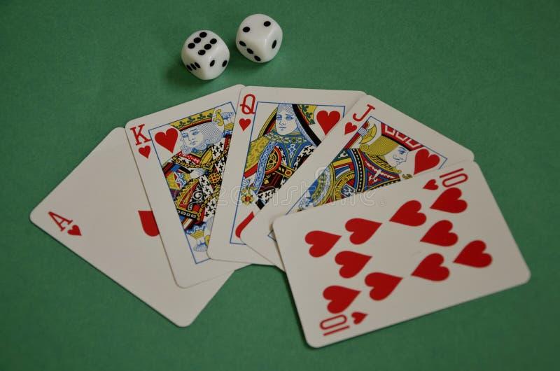 Aufgelockerter heraus roter Herz-Poker-Royal Flush und Würfel auf grünem Boi stockfoto
