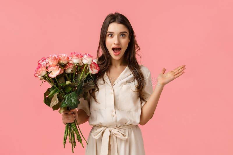 Aufgeregt und amüsant, überrascht wunderschöne moderne Frau in trendigem Kleid, verteilt die Hände seitwärts erstaunt und erstaun lizenzfreie stockbilder