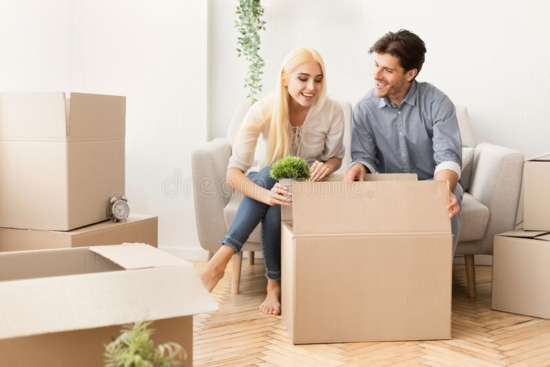 Aufgeregt verbinden Sie verpackendes Material in den Kästen, die für bewegliches Haus sich vorbereiten stockbild