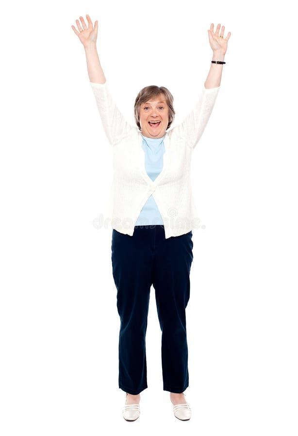 Aufgeregte ältere Frau, die mit den angehobenen Armen aufwirft lizenzfreies stockbild