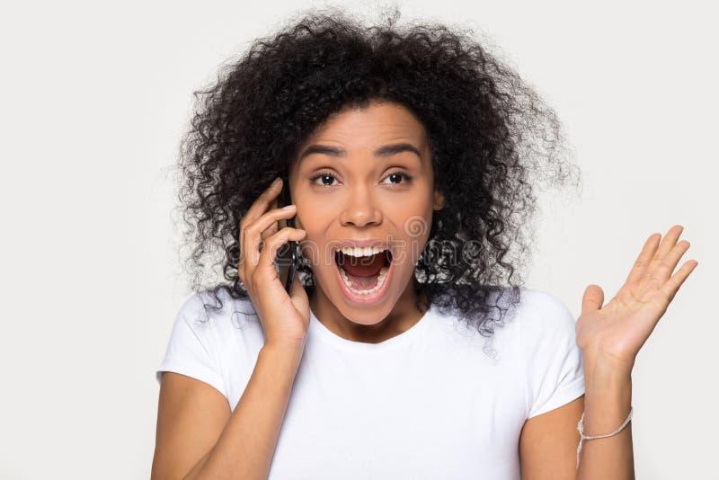 Aufgeregte überglückliche afrikanische Mädchenhörengute nachrichten, die am Telefon sprechen stockfotos