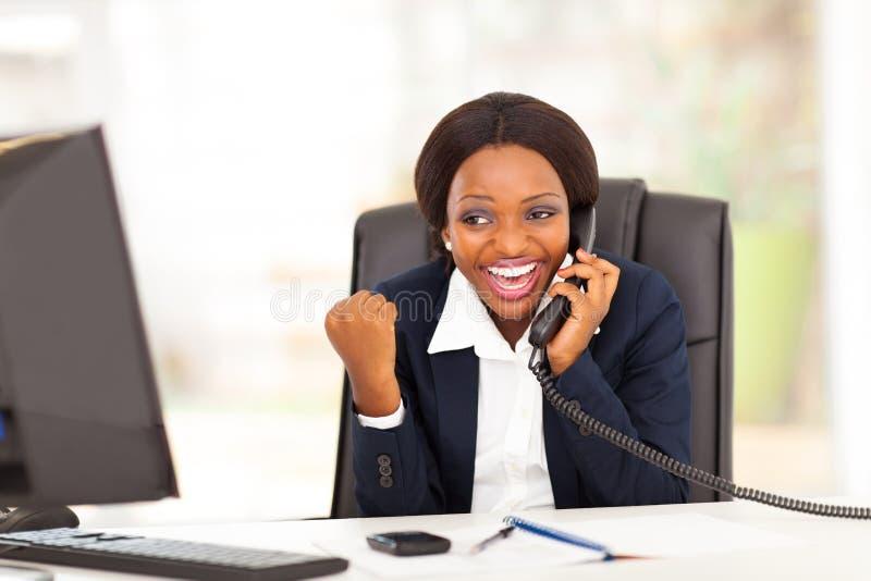 Aufgeregte afrikanische Geschäftsfrau stockfoto