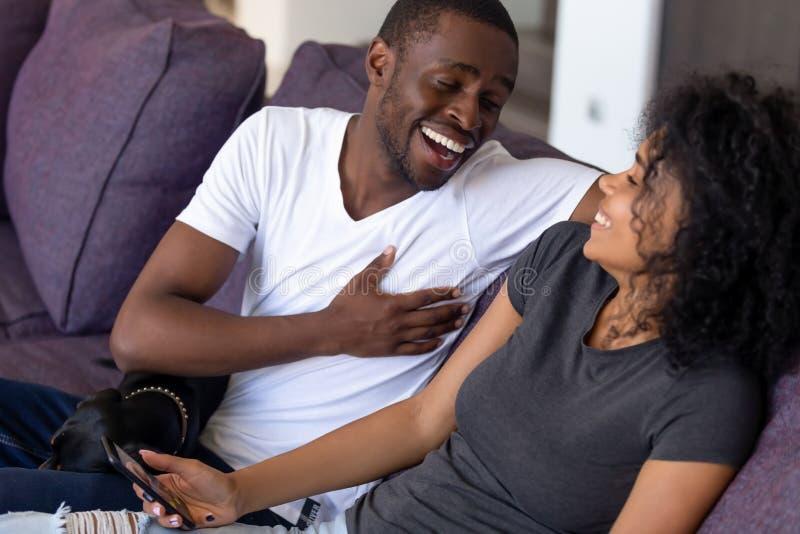 Aufgeregte Afroamerikanerpaare, die zusammen über lustigen Witz lachen stockfoto
