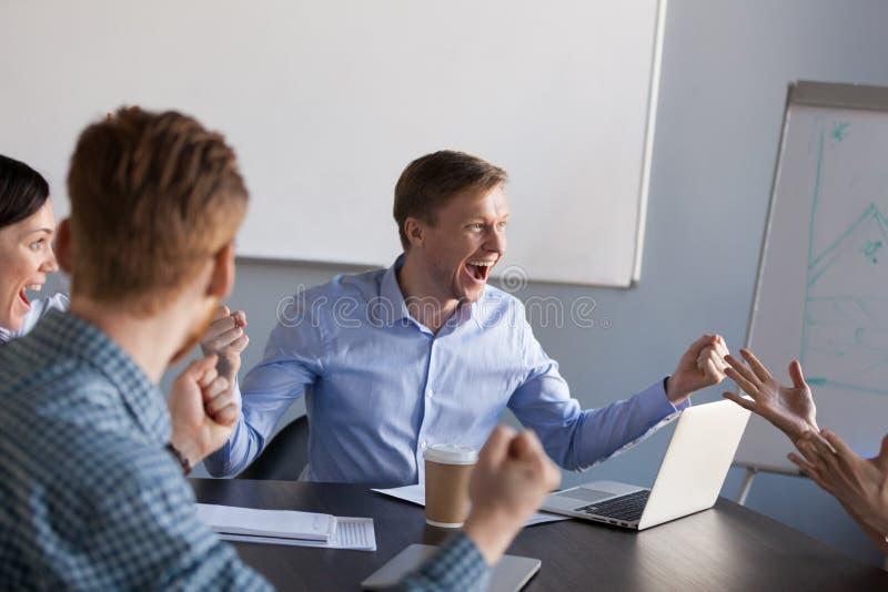 Aufgeregte Arbeitskräfte schreien für geteilte Unternehmenszielleistung lizenzfreies stockfoto