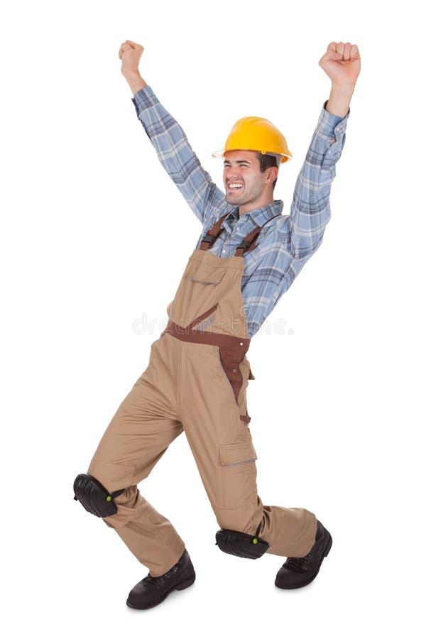 Aufgeregte Arbeitskraft, die harten Hut trägt lizenzfreies stockfoto