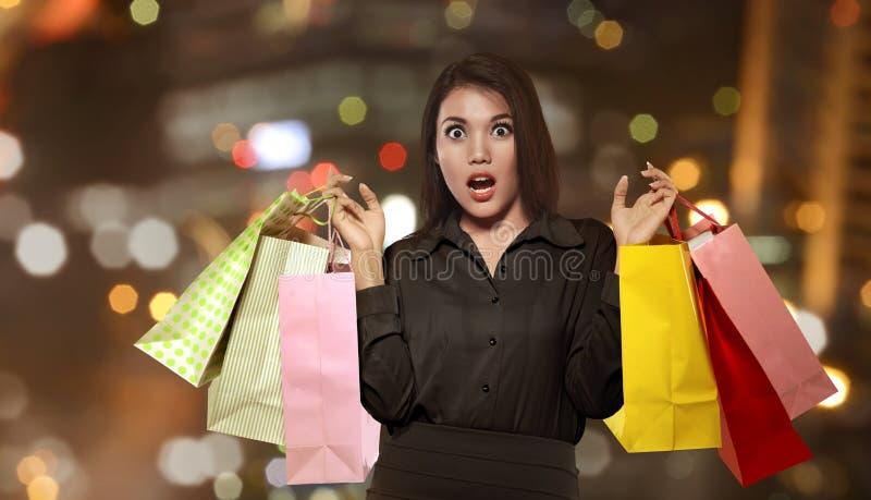 Aufgeregte asiatische Frau, welche die bunte Papiertüte feiert Schwarzes hält stockfotografie