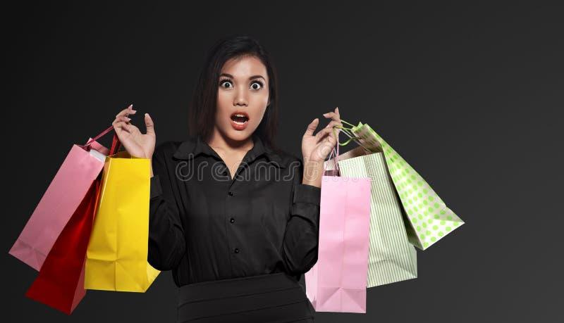 Aufgeregte asiatische Frau, welche die bunte Papiertüte feiert Schwarzes hält stockfotos