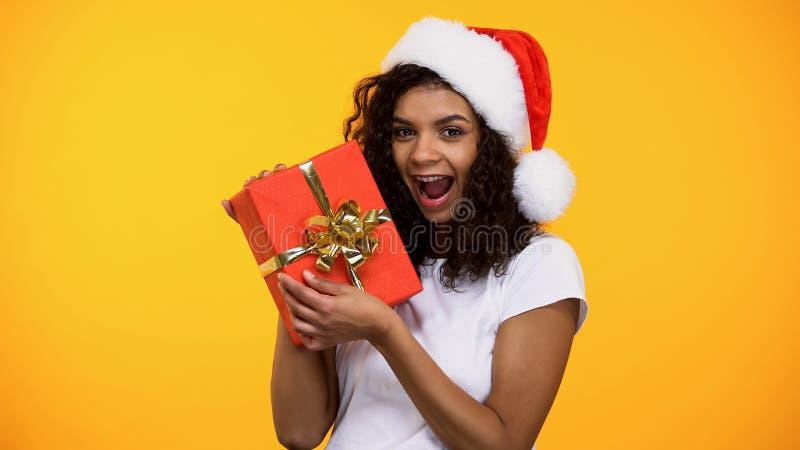 Aufgeregte attraktive Frau, die rote Geschenkbox, anwesenden Feiertagsgruß des neuen Jahres hält lizenzfreies stockfoto