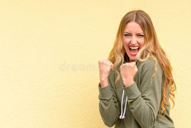 Aufgeregte blonde Frau, die ihre Fäuste zusammenpressend zujubelt stockbild