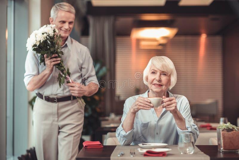 Aufgeregte Dame, die auf einen Mann in einem Café wartet stockfoto
