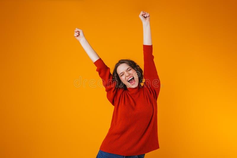 Aufgeregte emotionale glückliche junge hübsche Frauenaufstellung lokalisiert über gelbem Wandhintergrund lizenzfreie stockfotografie