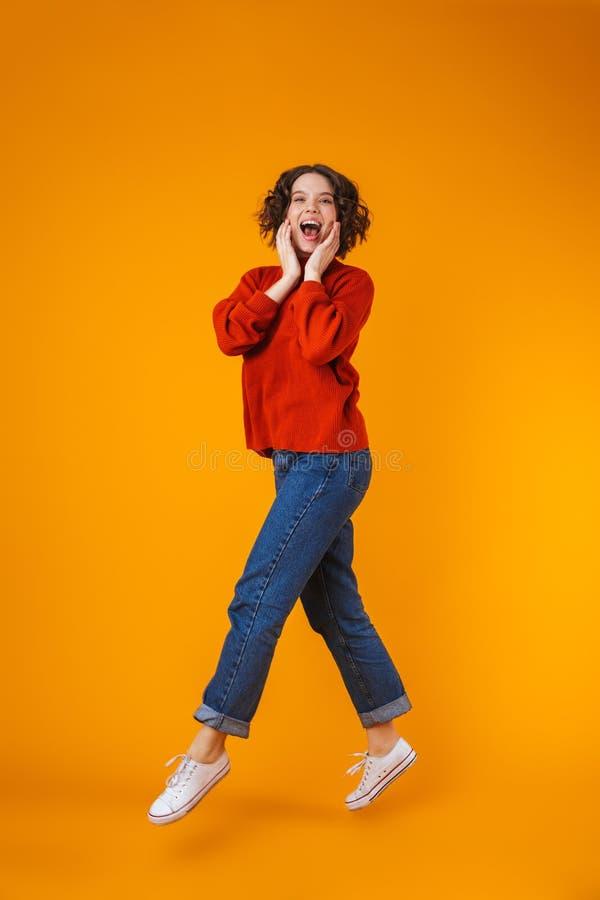 Aufgeregte emotionale glückliche junge hübsche Frauenaufstellung lokalisiert über gelbem Wandhintergrund stockfotografie