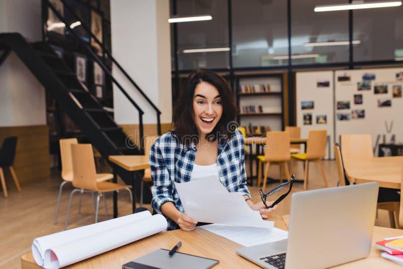Aufgeregte erstaunte junge brunette Frau umgeben bei Tisch das Arbeitsmaterial, das positive Gefühle in der Bibliothek ausdrückt  lizenzfreie stockbilder