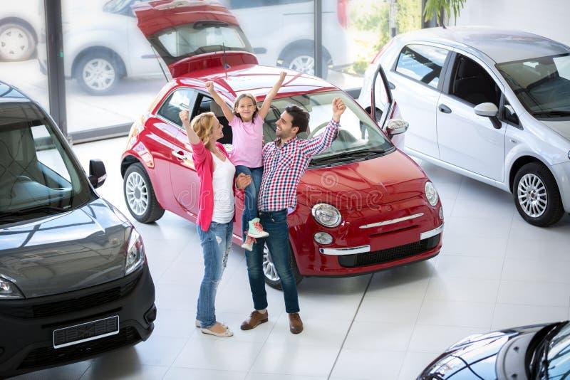 Aufgeregte Familie, die einen Neuwagen kauft lizenzfreie stockfotos