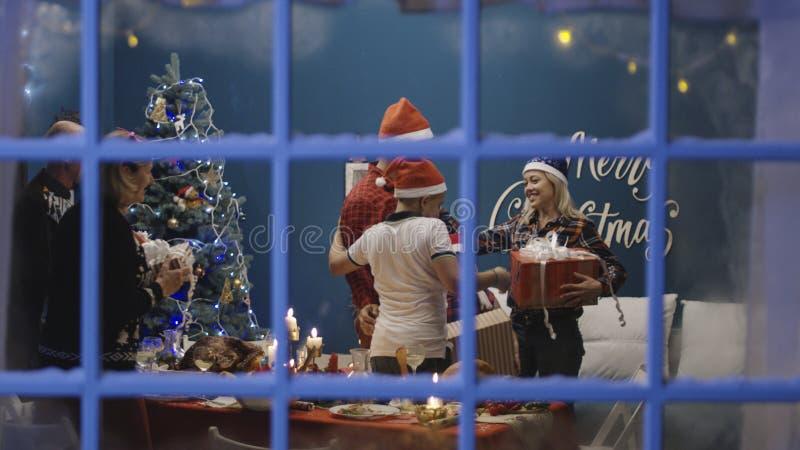 Aufgeregte Familie, die mit Geschenken am Weihnachten austauscht stockfotos