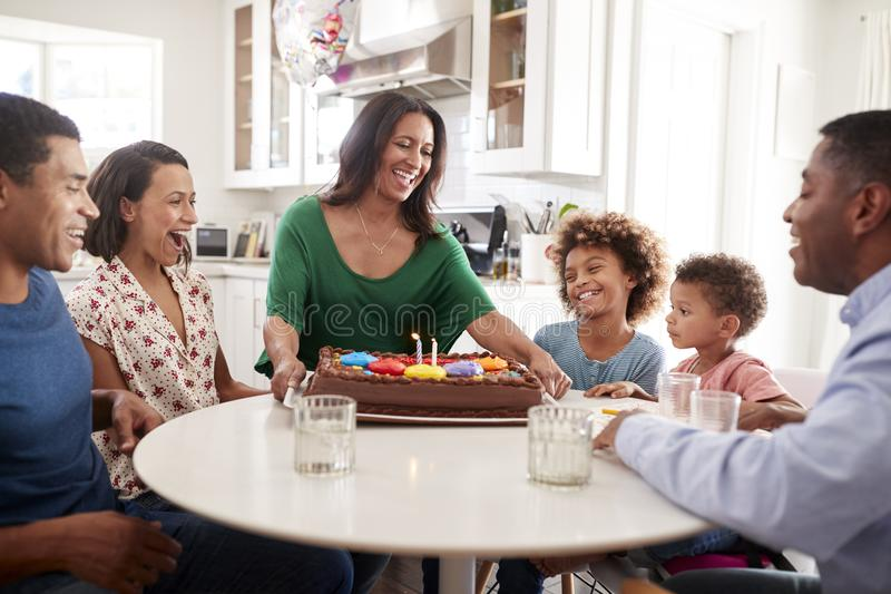 Aufgeregte Familie mit drei Generationen, die zusammen in der Küche feiert einen Geburtstag, Großmutter holt den Kuchen zum Tabel stockbild