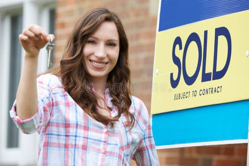 Aufgeregte Frau außerhalb des neuen Hauses, das Schlüssel hält lizenzfreie stockbilder