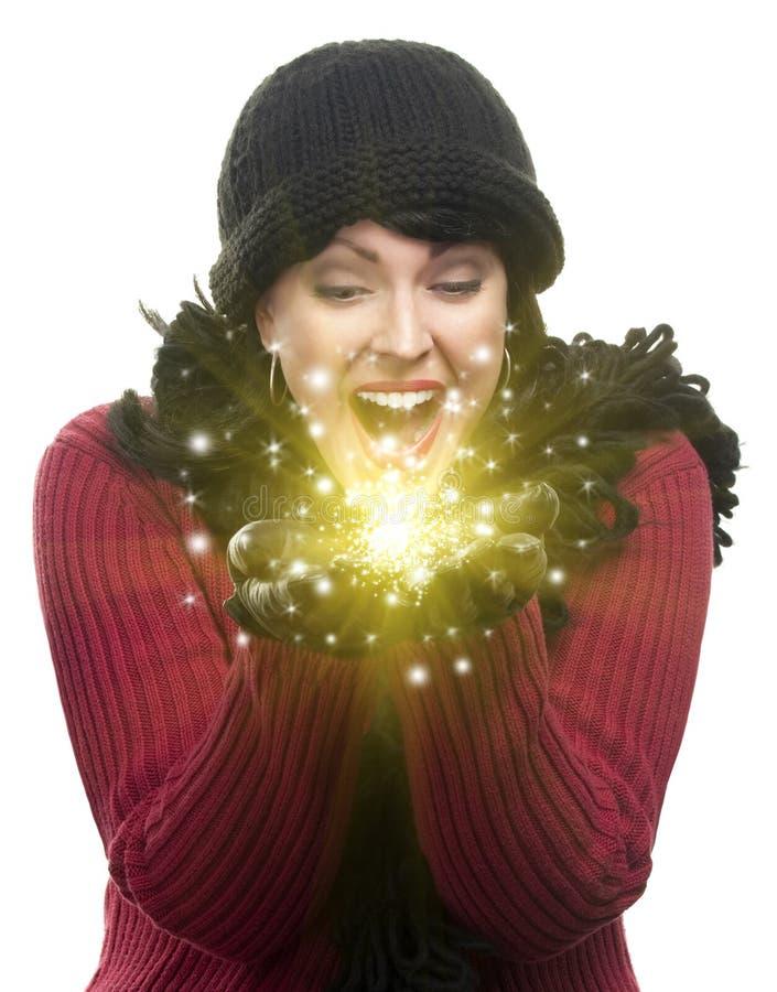 Aufgeregte Frau in den Winter-Kleidungs-Griffen etwas, das in Han funkelt lizenzfreie stockbilder