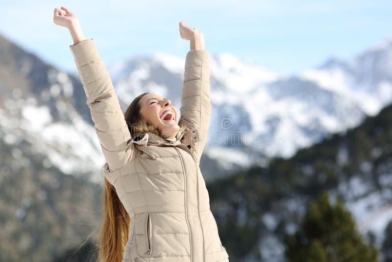 Aufgeregte Frau, die Arme im schneebedeckten Berg anhebt lizenzfreies stockbild
