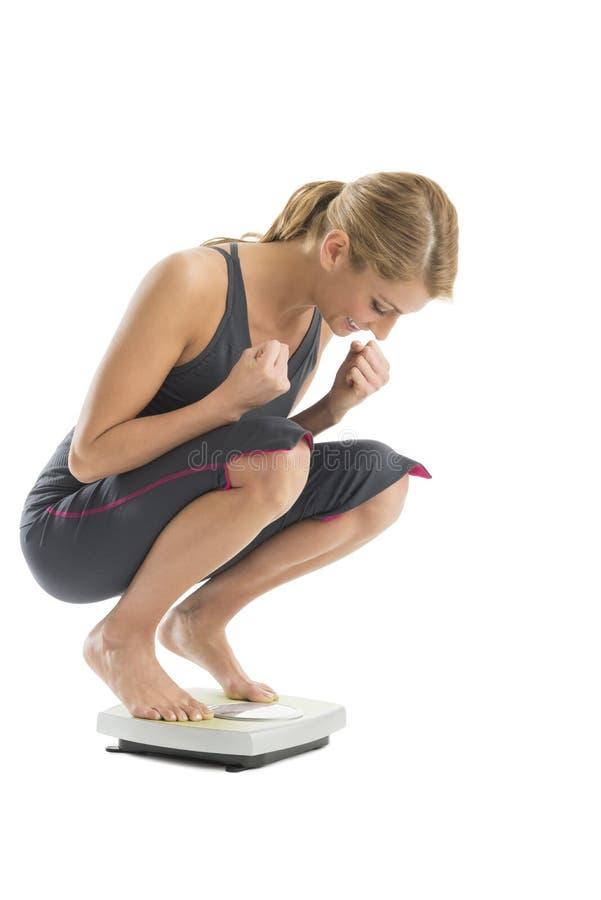 Aufgeregte Frau, die auf Gewichts-Skala sich wiegt lizenzfreies stockbild