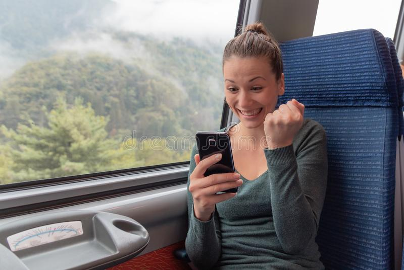 Aufgeregte Frau, die einen Smartphone hält und im Zug auf Linie Reise gewinnt stockfotos