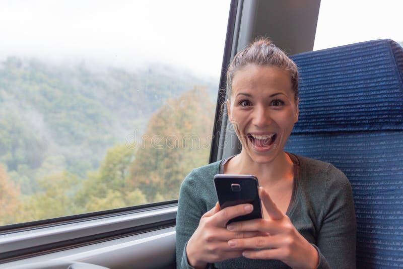 Aufgeregte Frau, die einen Smartphone h?lt und im Zug auf Linie Reise gewinnt stockbilder