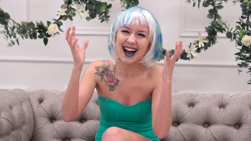 Aufgeregte Frau, die Sie zu Hause sitzend auf einem Sofa im Wohnzimmer betrachtet stockfoto
