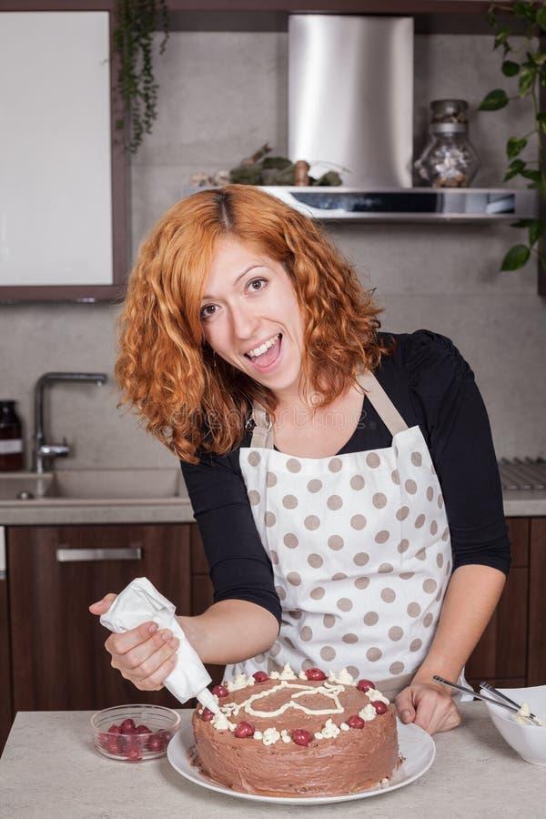 Aufgeregte Frau, die zu Hause Kuchen verziert stockfotografie