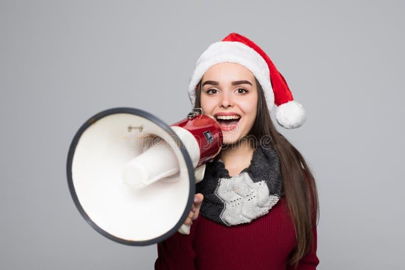 Aufgeregte Frau in Sankt-Hut, der Megaphon über grauem Hintergrund hält stockbild