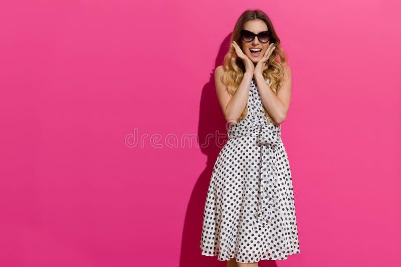 Aufgeregte Frau steht im Sonnenlicht und hält Haupt in den Händen lizenzfreie stockfotos