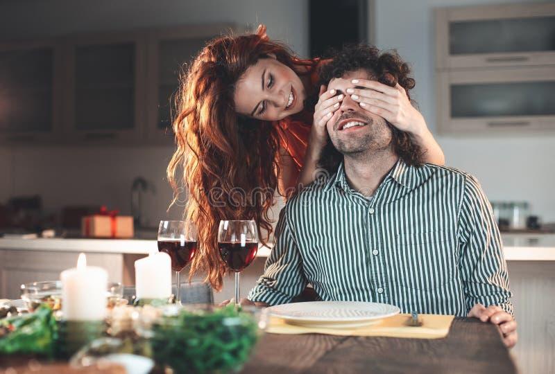 Aufgeregte Frau vorbereitete Überraschung für Mann zu Hause lizenzfreies stockbild