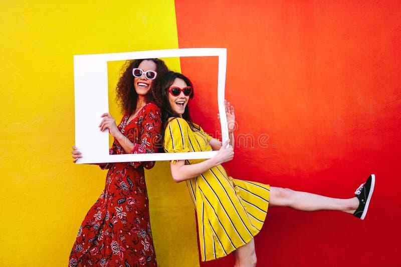Aufgeregte Freundinnen mit leerem Fotorahmen stockfoto