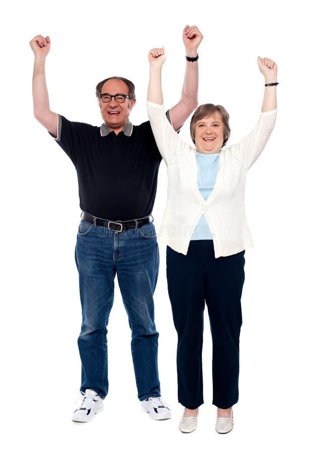Aufgeregte gealterte Paare, die mit den angehobenen Armen aufwerfen lizenzfreie stockbilder