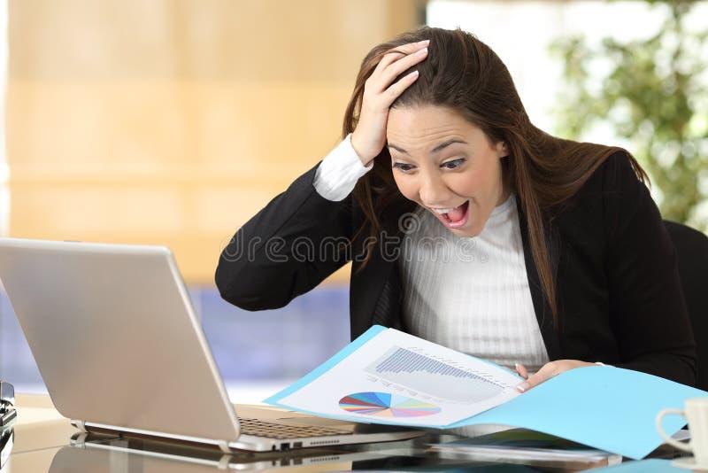 Aufgeregte Geschäftsfrau, die Diagramm im Büro überprüft stockfoto