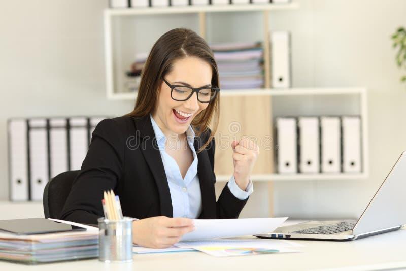 Aufgeregte Geschäftsfrau, die gorwth Diagramm im Büro überprüft stockfoto