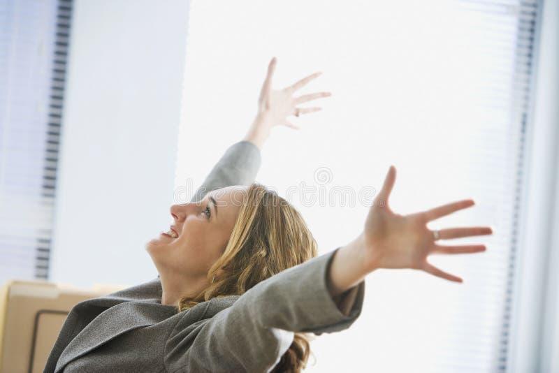 Aufgeregte Geschäftsfrau, die im Büro sitzt stockfotos
