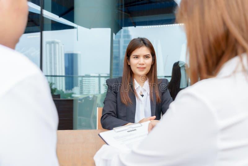Aufgeregte Geschäftsfrau oder Kandidat, die von den Managern interviewt wird stockfoto