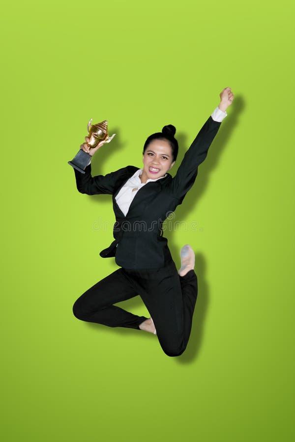 Aufgeregte Geschäftsfrau springt mit Trophäe auf Studio stockbild