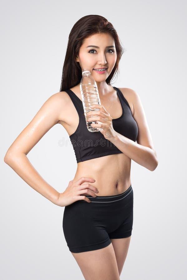 Aufgeregte junge asiatische Frau, die eine Flasche Wasser nach dem Handeln zeigt stockbild